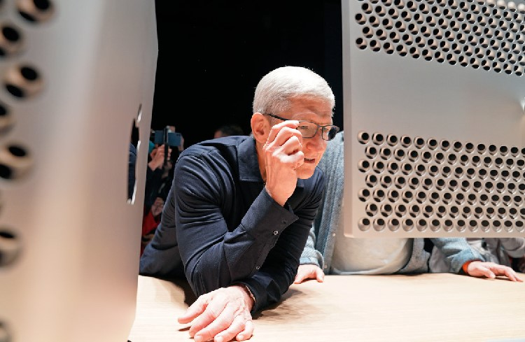 Apple CEO Tim Cook inspects one of the company