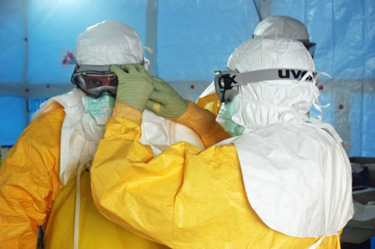 Health care workers put on protective gear before entering an Ebola treatment unit in Liberia
