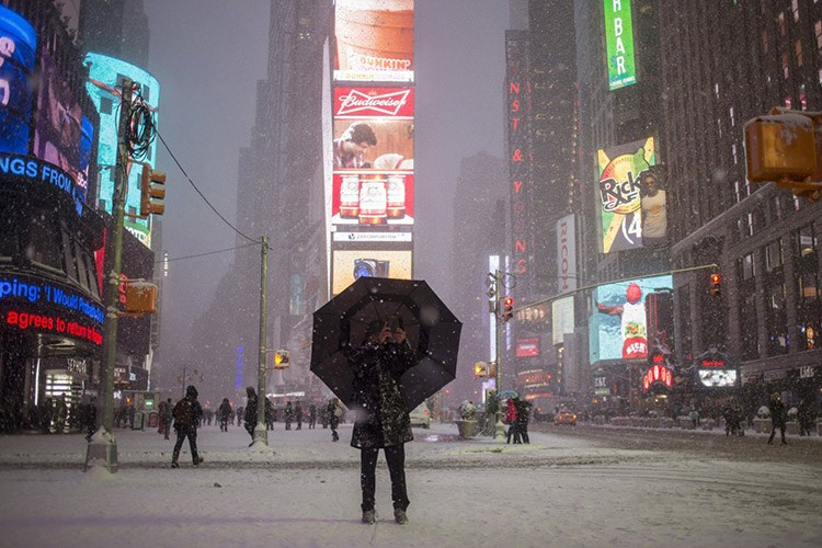 13 a man stands under an umbrella while photographing a snow storm in times square new york s f06c8