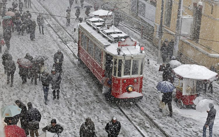 18 people brave the cold and snow as they walk in the main pedestrian street of istiklal in central istanbul s 50b49